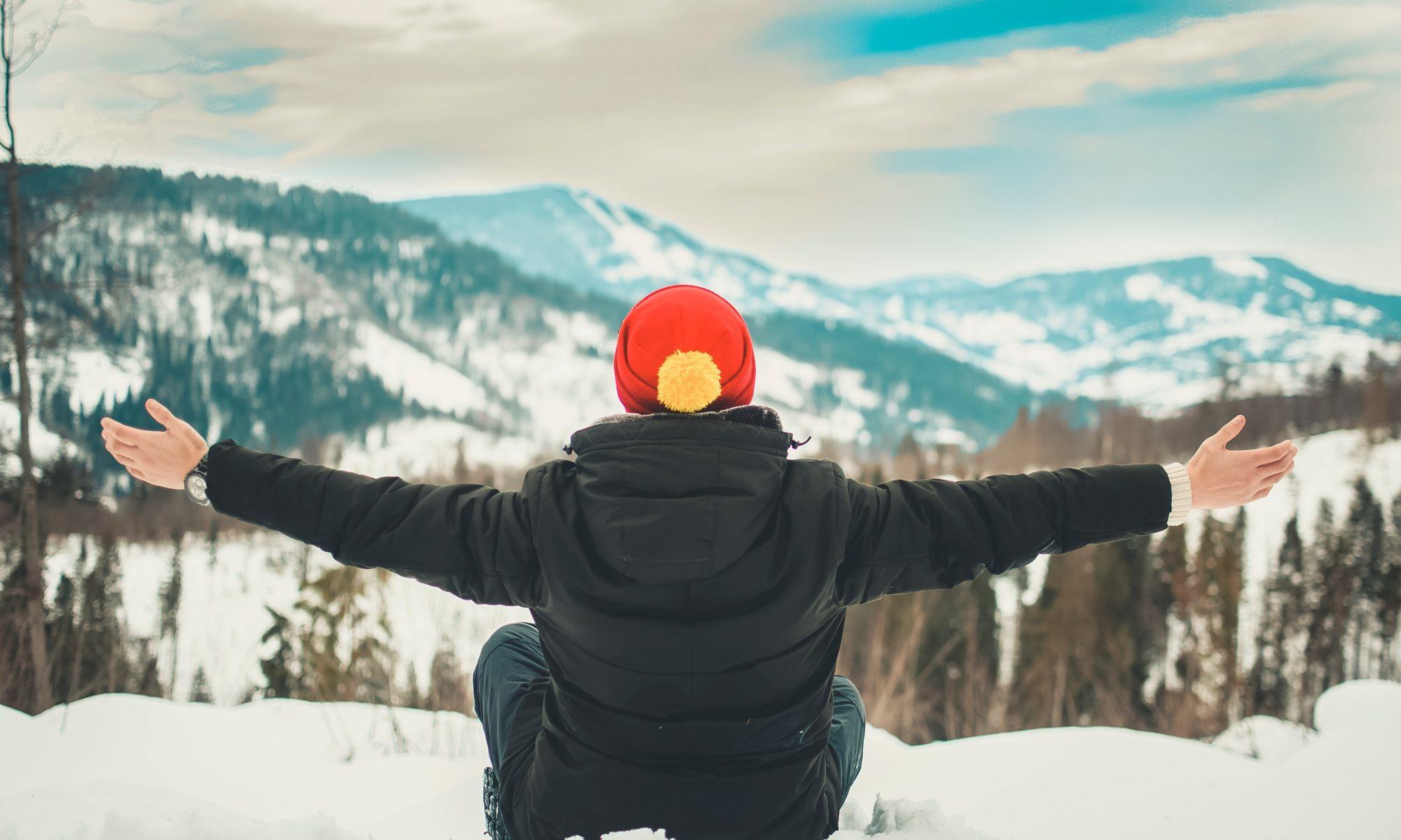 Sentado en la nieve con chaqueta y gorro