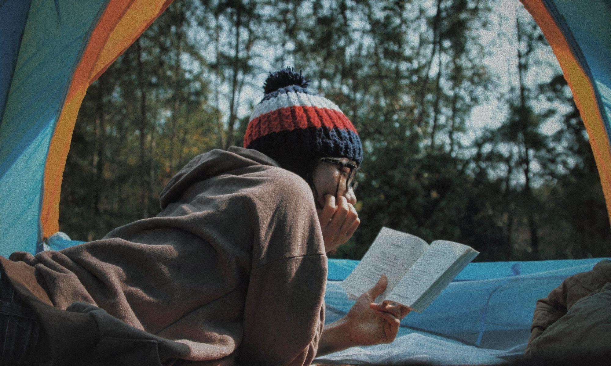 Leyendo un libro dentro de una tienda de campaña